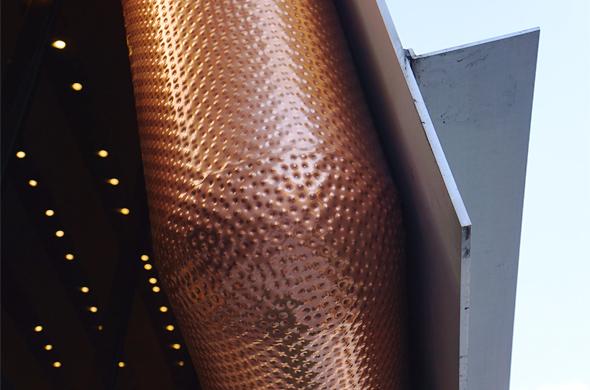 囲の色を控えめに反射させているステンレス製の外壁と雨水受けのアップ。こちらも繊細なディティールだ。